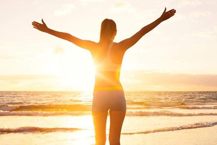 Frau am Strand voller Lebensfreude breitet die Arme aus.